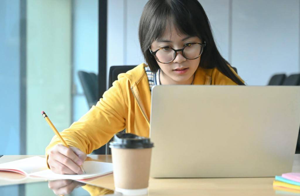 A female student with glasses is lacquer a lesson from her online study at home.