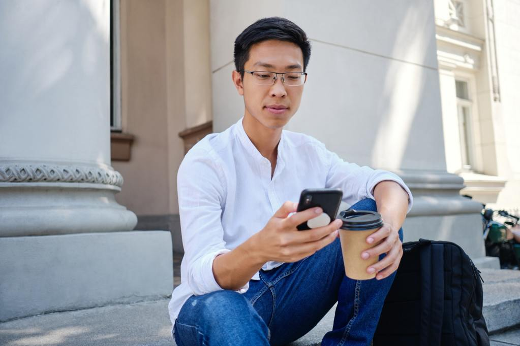 Asian student in eyeglasses with coffee to go thoughtfully using cellphone near university