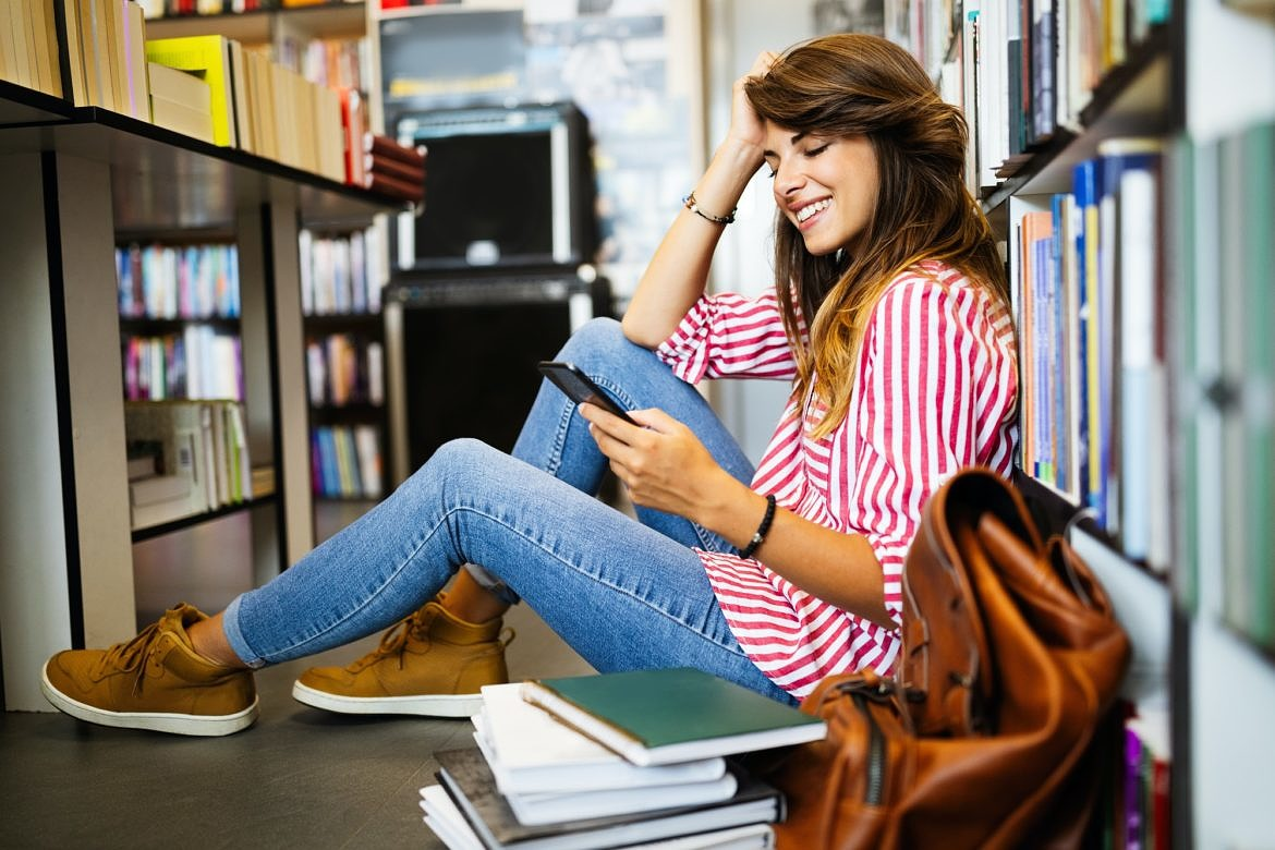 Happy student woman using phone instead of learning in library