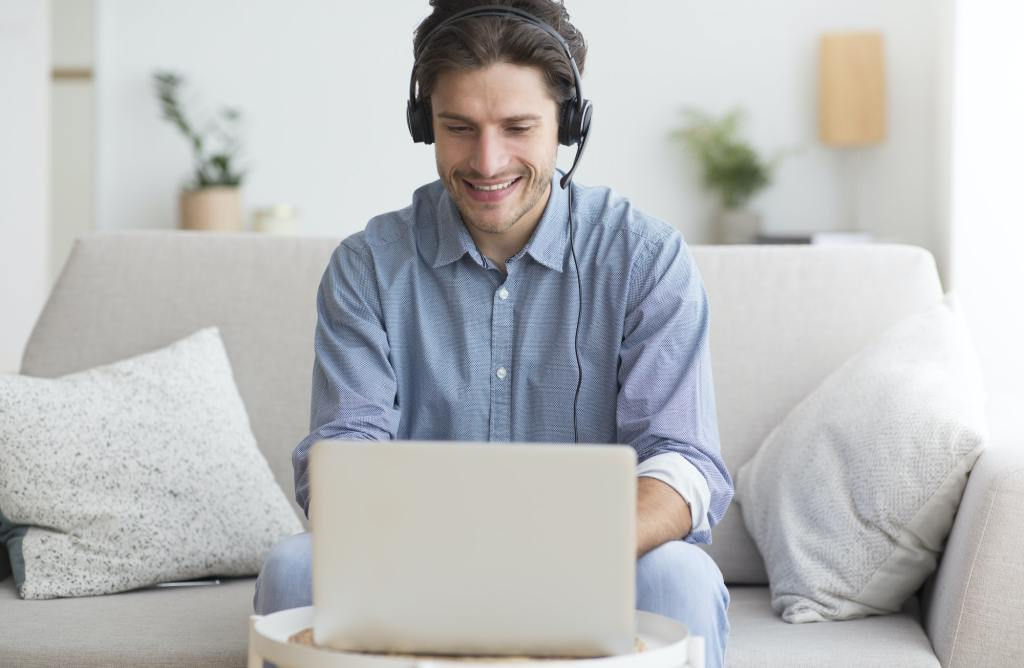 Man In Earphones Using Laptop Listening To Podcast At Home
