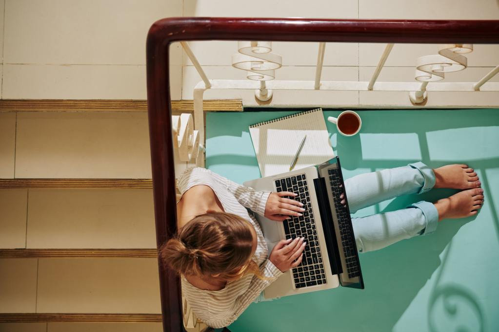 Woman With Laptop On Staircase