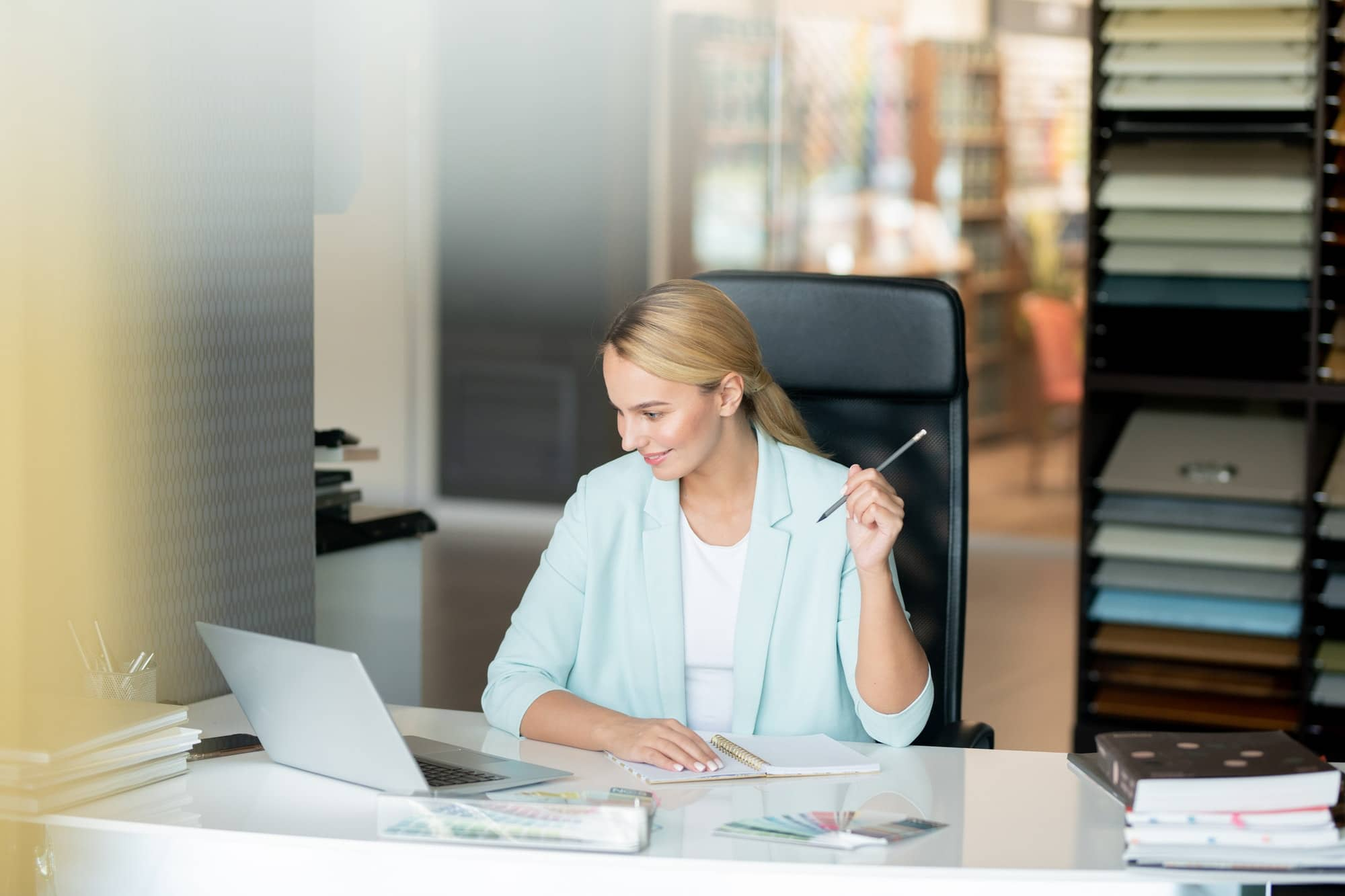 Clever young female student sitting by desk while watching online video