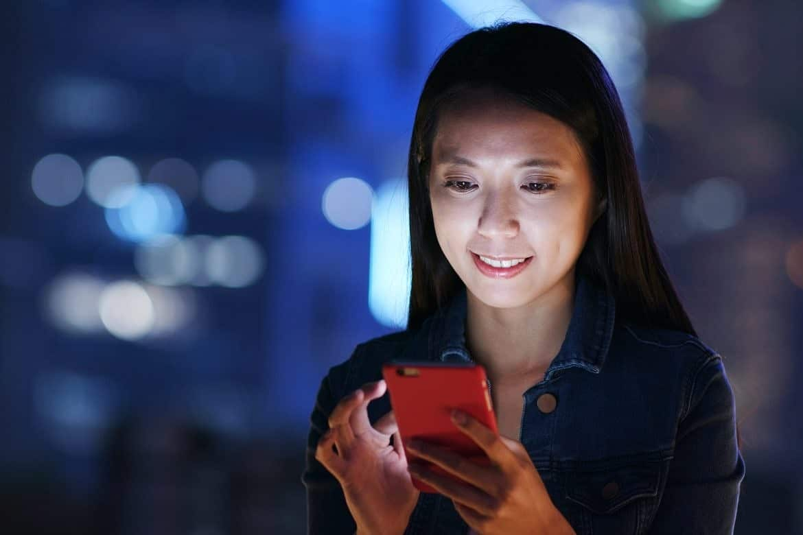Woman work on smart phone over business district at night